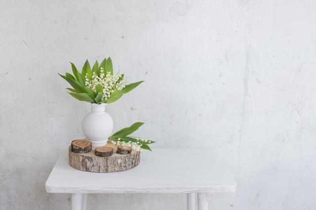 배경 오래 된 흰 벽에 꽃병에 은방울꽃