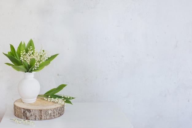 오래 된 흰 벽에 꽃병에 은방울꽃