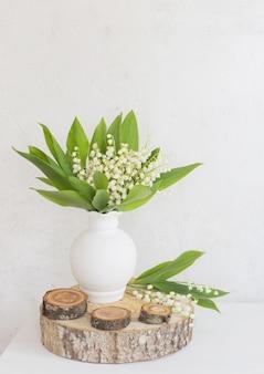 표면 오래 된 흰 벽에 꽃병에 은방울꽃