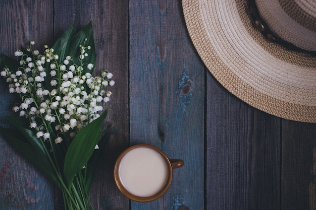 Lily of the valley bouquet, cup of coffee, tea, milk, on wooden background