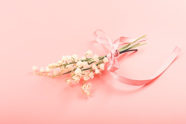 Lily of the valley bouquet tied with a pink ribbon on a pink background delicate spring concept