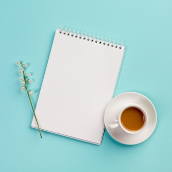 Lily of the valley flower twig on white spiral notepad with coffee cup on blue backdrop