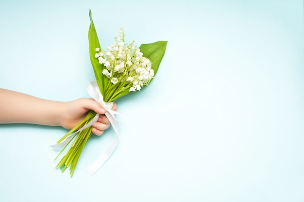 Lily of the valley flowers. child hand holding a bouquet of lily of the valley flowers on blue background. flat lay, top view, copy space.