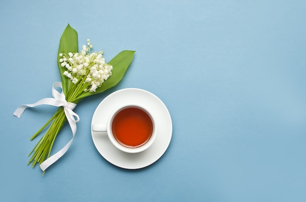 Lily of the valley flowers and cup of tea on blue background