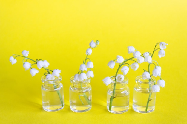 Lily of the valley flowers in glass jars on a yellow