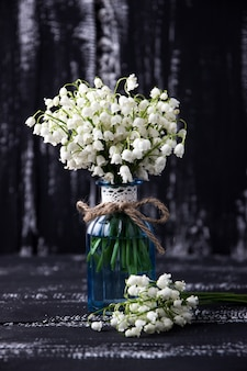 Lily of the valley on wooden background. lily of the valley bouquet. space for text.