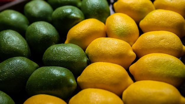 시장 카운터에 라임과 레몬 배경입니다. 지역 농부 식품 슈퍼마켓에서 신선한 유기농 레몬. 식료품 선반에 있는 판지 상자에 있는 과일의 보기를 닫습니다.