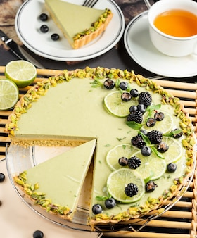 Lime cheesecake garnished with lime slices, blackberry, black currant and pistachios