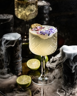 Lime cocktail garnished with lime and flower petals in long stem glass