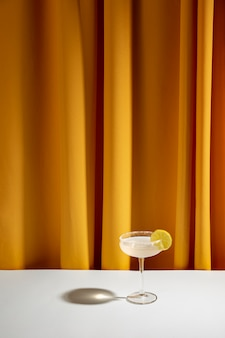 Lime cocktail in saucer glass on white table against yellow curtain
