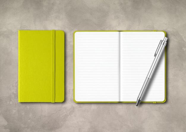 Желто-зеленые тетради с закрытой и открытой линовкой и ручкой. макет, изолированные на бетонном фоне