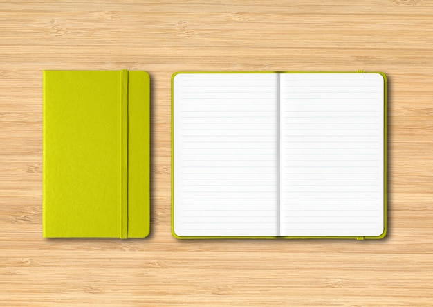 Lime green closed and open lined notebooks  isolated on wooden table