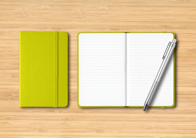 Lime green closed and open lined notebooks with a pen.  isolated on wooden background