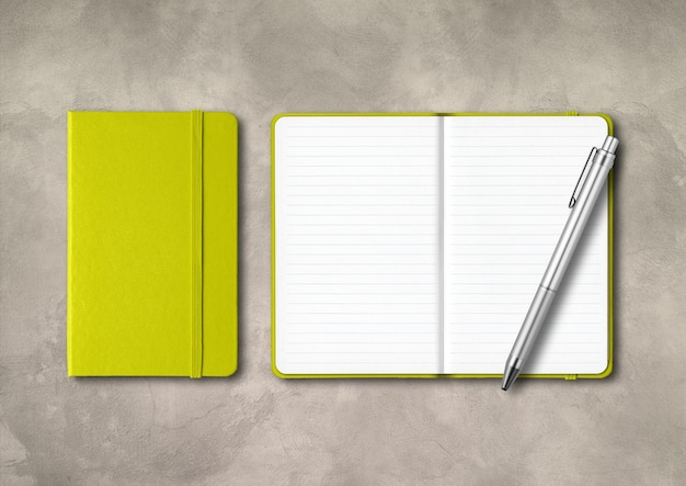 Lime green closed and open lined notebooks with a pen . mockup isolated on concrete background