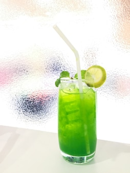 Lime green soda with ice in classic glass with white straw on white table and glass background
