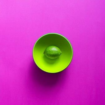 Известь в зеленой миске на фиолетовой стене. плоская планировка.