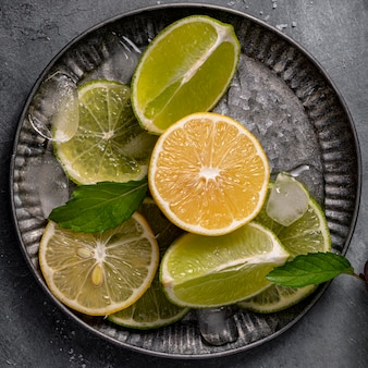 Lime and lemon slices on plate flat lay