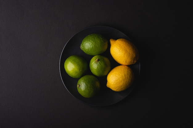 Lime and lemon sour fruits in black plate on moody dark