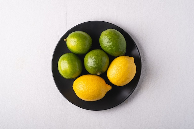Lime and lemon sour fruits in black plate on white background, top view, vitamins and healthy food