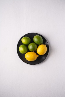 Lime and lemon sour fruits in black plate on white