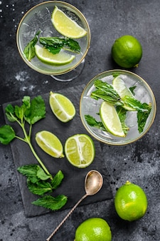 Lime lemonade with mint and ice. black background. top view.