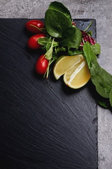 Lime, lettuce, greens and red cherry tomatoes lie on a dark stone slate background