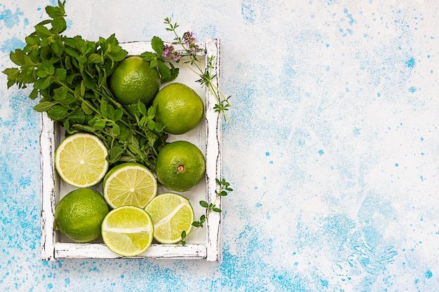 Lime and mint on light wooden tray, blue concrete background. summer concept. top view. copy space.