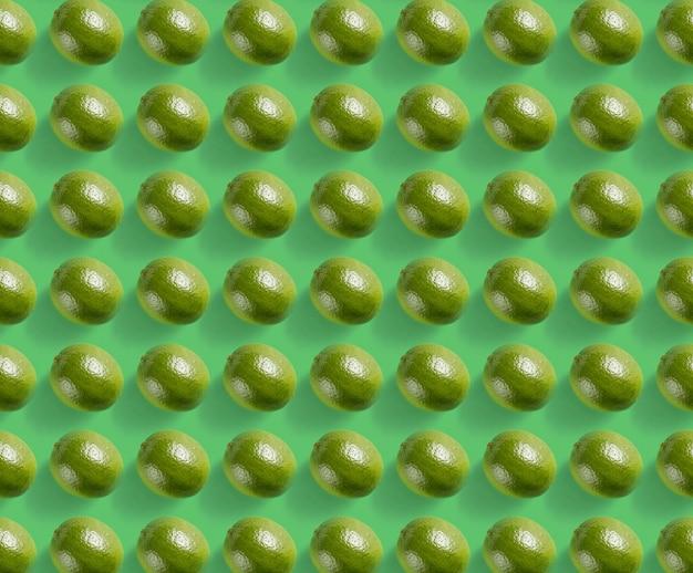 Лаймовый узор с жесткой тенью на зеленом фоне, вид сверху.