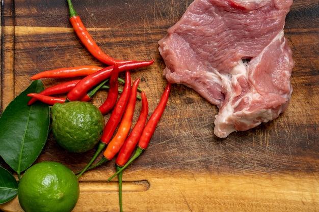 Лайм, красный перец чили и свинина на фоне деревянной разделочной доски