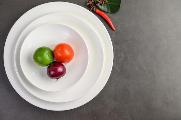 Лайм, красный лук и помидоры на белой тарелке.