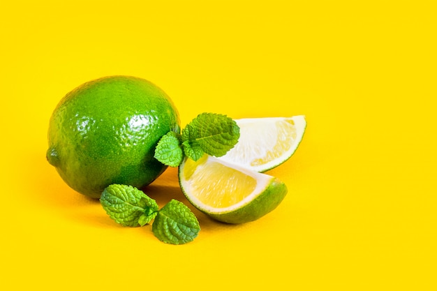 Lime slices and green mint leaves on a yellow