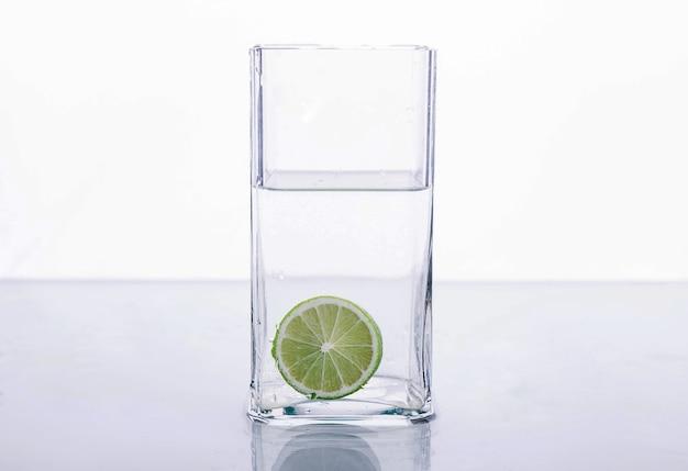 白い背景の上の水のガラスに飛び散るライム