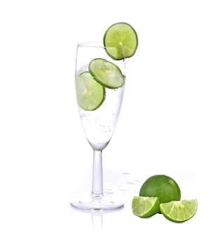 Lime splashing into glass of soda on white