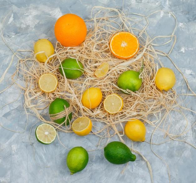 회색 대리석 표면에 라임, 레몬, 오렌지