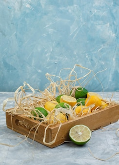 Limes and lemons in a wooden crate on a grey and blue marble surface