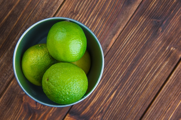 Limes in a mini bucket on a wooden table. flat lay.