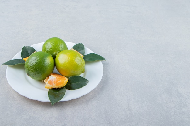 Limes and tangerine slices on white plate.