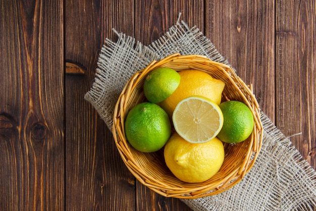 Limes in a wicker basket with lemons flat lay on wooden and piece of sack