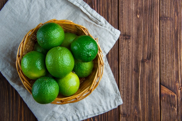 Limes in a wicker basket on wooden and kitchen towel, flat lay.