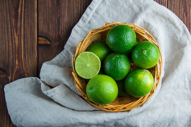 Limes in a wicker basket on wooden and kitchen towel. flat lay.