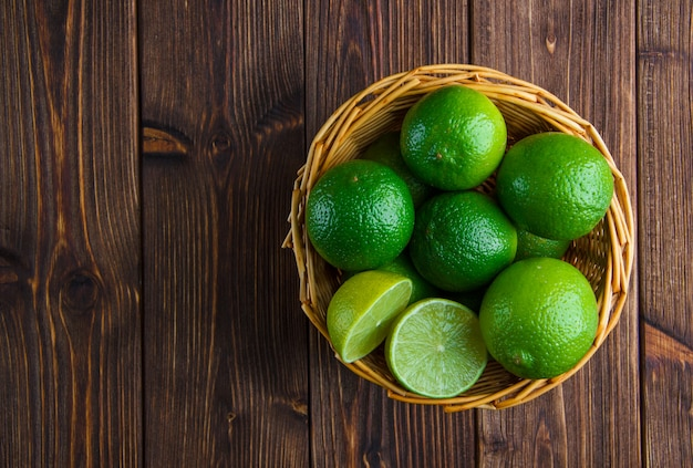 Limes in a wicker basket on wooden table. flat lay.
