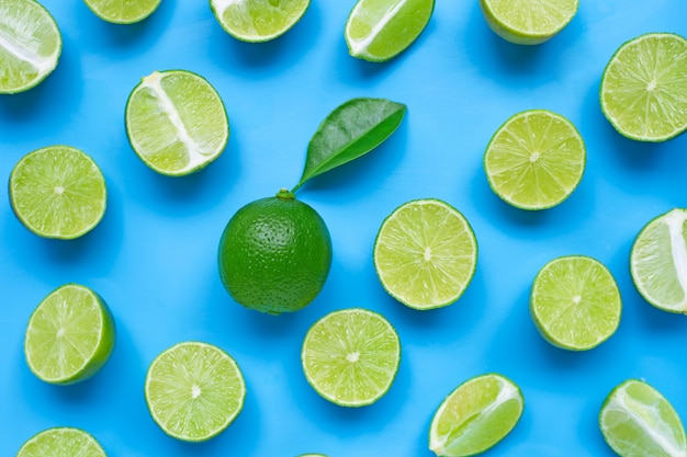 Limes with leaf on blue. top view