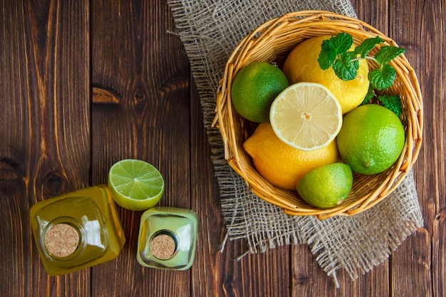 Limes with lemons, soft drinks, herbs in a wicker basket on wooden and piece of sack, flat lay.
