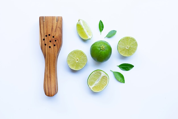 Limes with wooden lime squeezer on white.