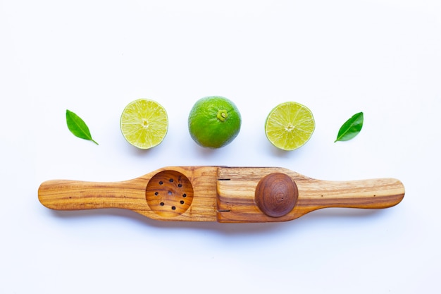 Limes with wooden lime squeezer on white