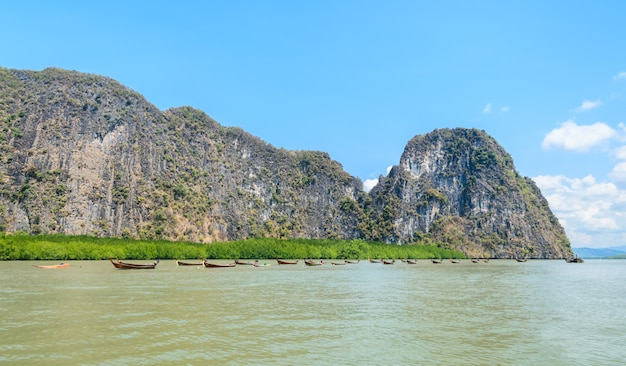 Limestone island with mangrove forest and long-tail wooden boats in phang nga bay national park, thailand