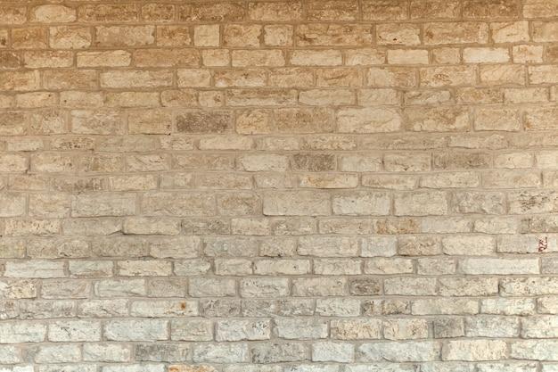 석회암 천연 벽돌 벽. 크림색과 흰색 벽돌 벽 질감 배경입니다. 벽돌 쌓기 또는 석조 바닥 내부는 오래된 패턴의 석재 디자인 스택입니다.