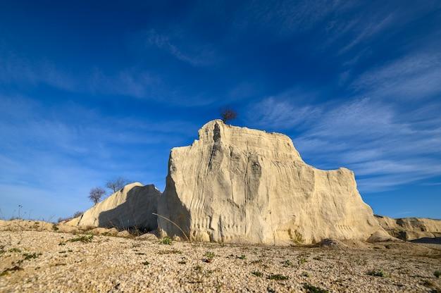Известняковая скала с деревом на вершине известнякового карьера