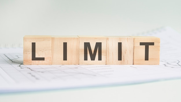 Лимит написан на легких деревянных брусках. слово находится на листе с диаграммами и графиками. бизнес-концепция. серый фон