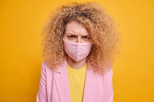 바이러스 확산 위험을 제한하십시오. 공식적인 옷을 입은 불쾌한 여성은 코로나 바이러스가 노란색 벽 위에 고립 된 바이러스 백신이 필요하지 않도록 보호 마스크를 착용합니다. 전염병 발생 격리